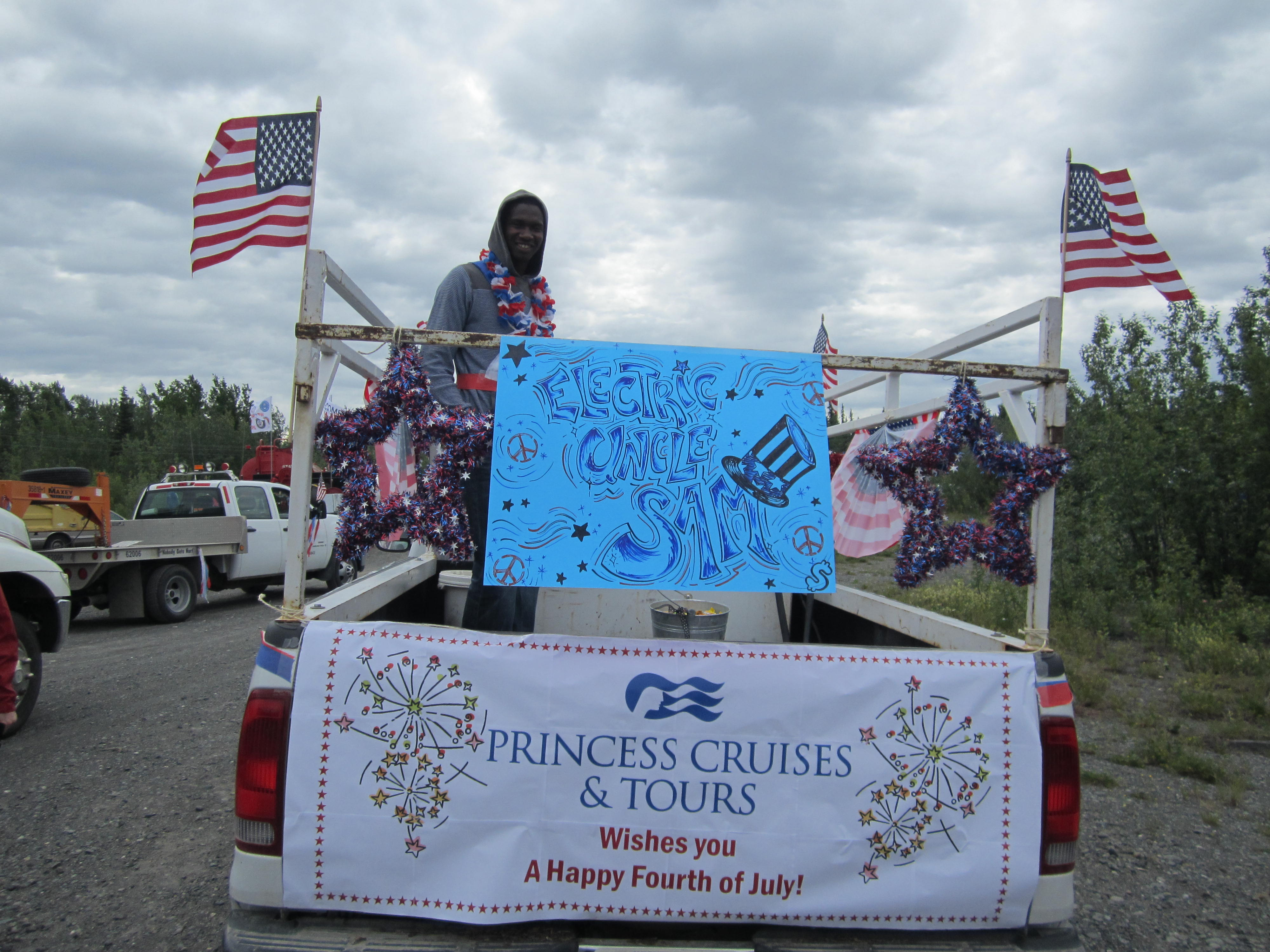 "photo of employee in the truck decorated with red white and blue and ""Electric Uncle Sam"" and Princess wishes you a happy Fourth of July"" signs."