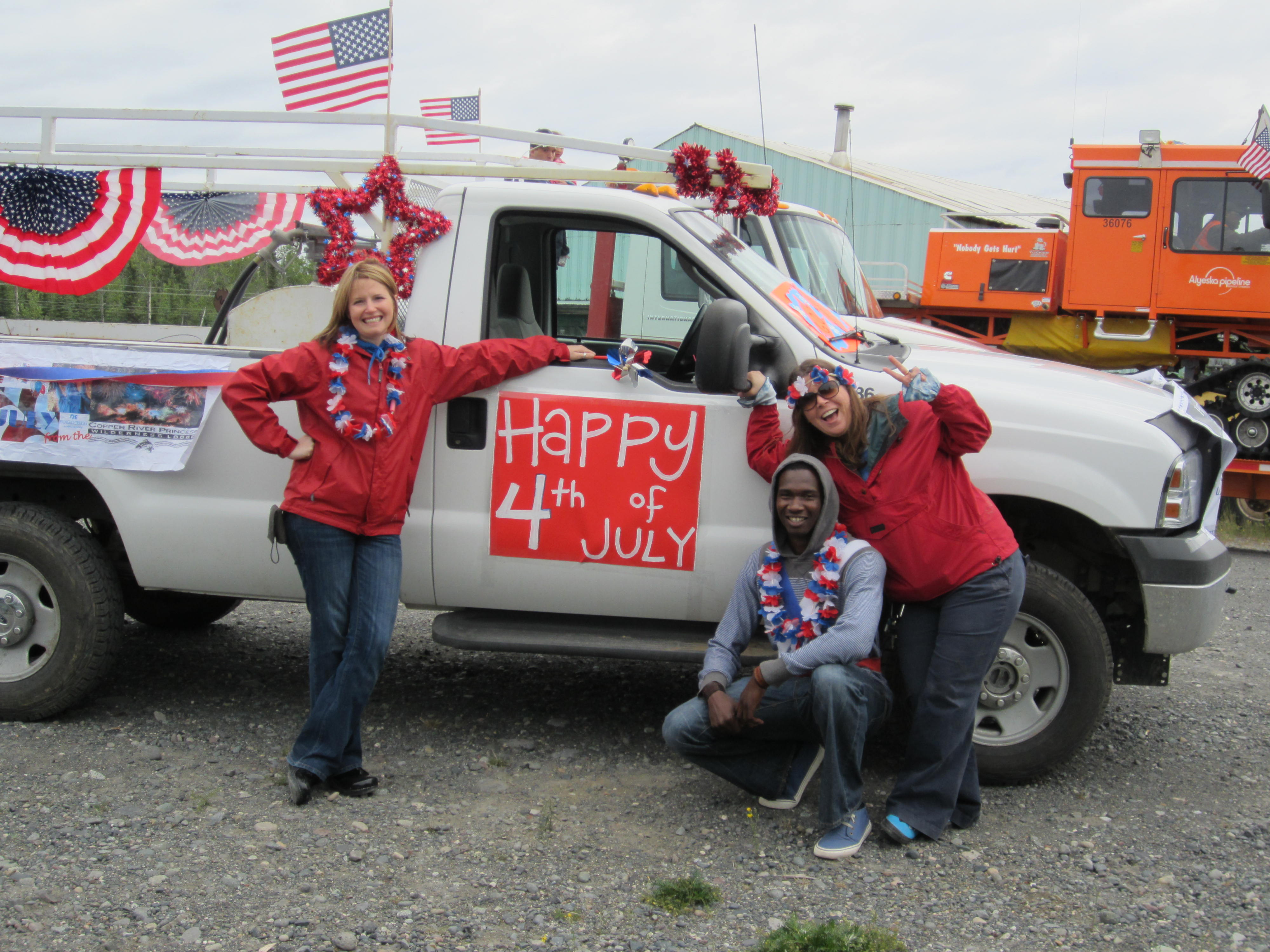 More employees posing with the red white and blue decorated truck for the Fourth of July Parade.