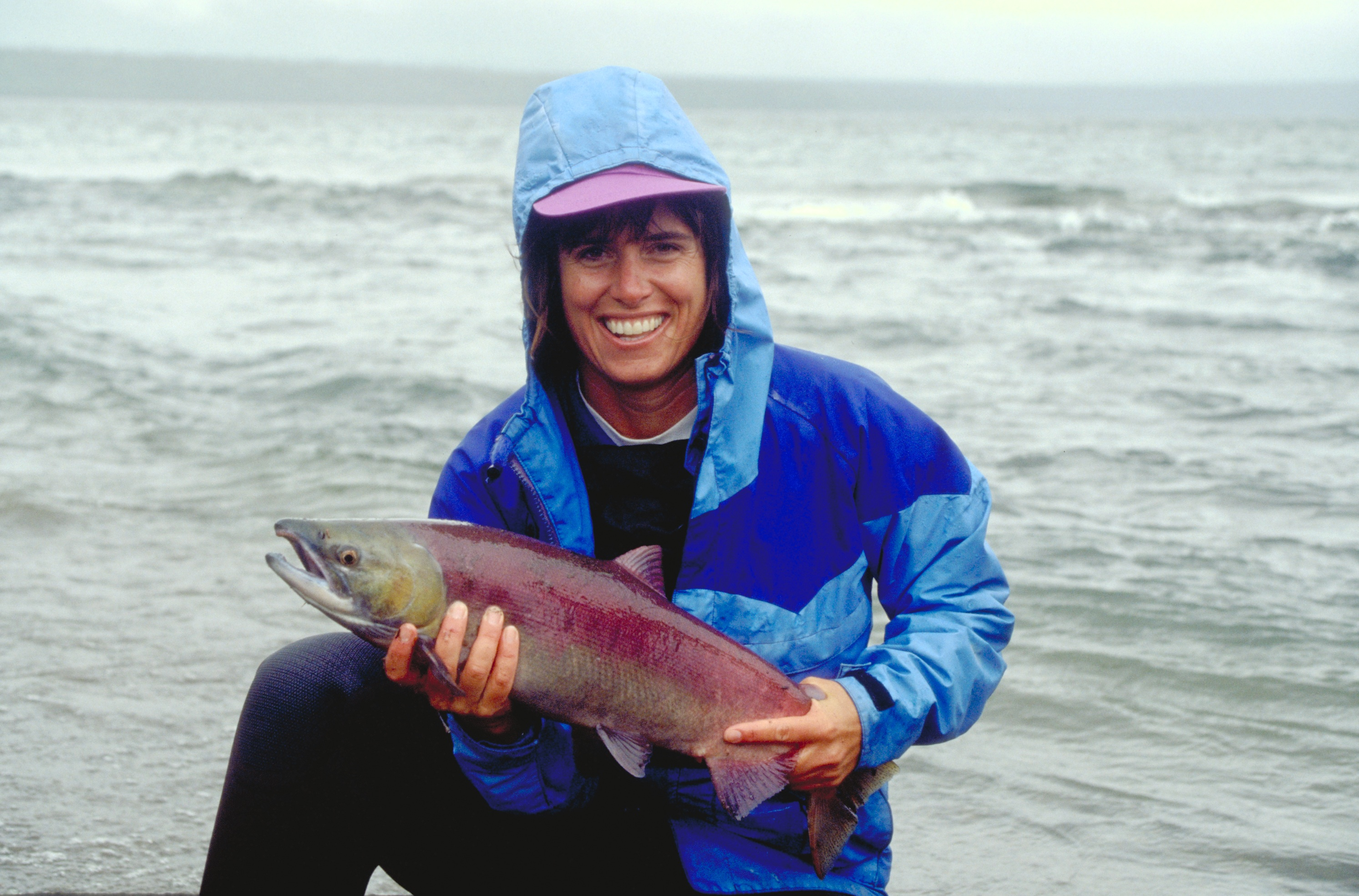 Alaskan salmon held by a woman with a big smile and a blue rain coat