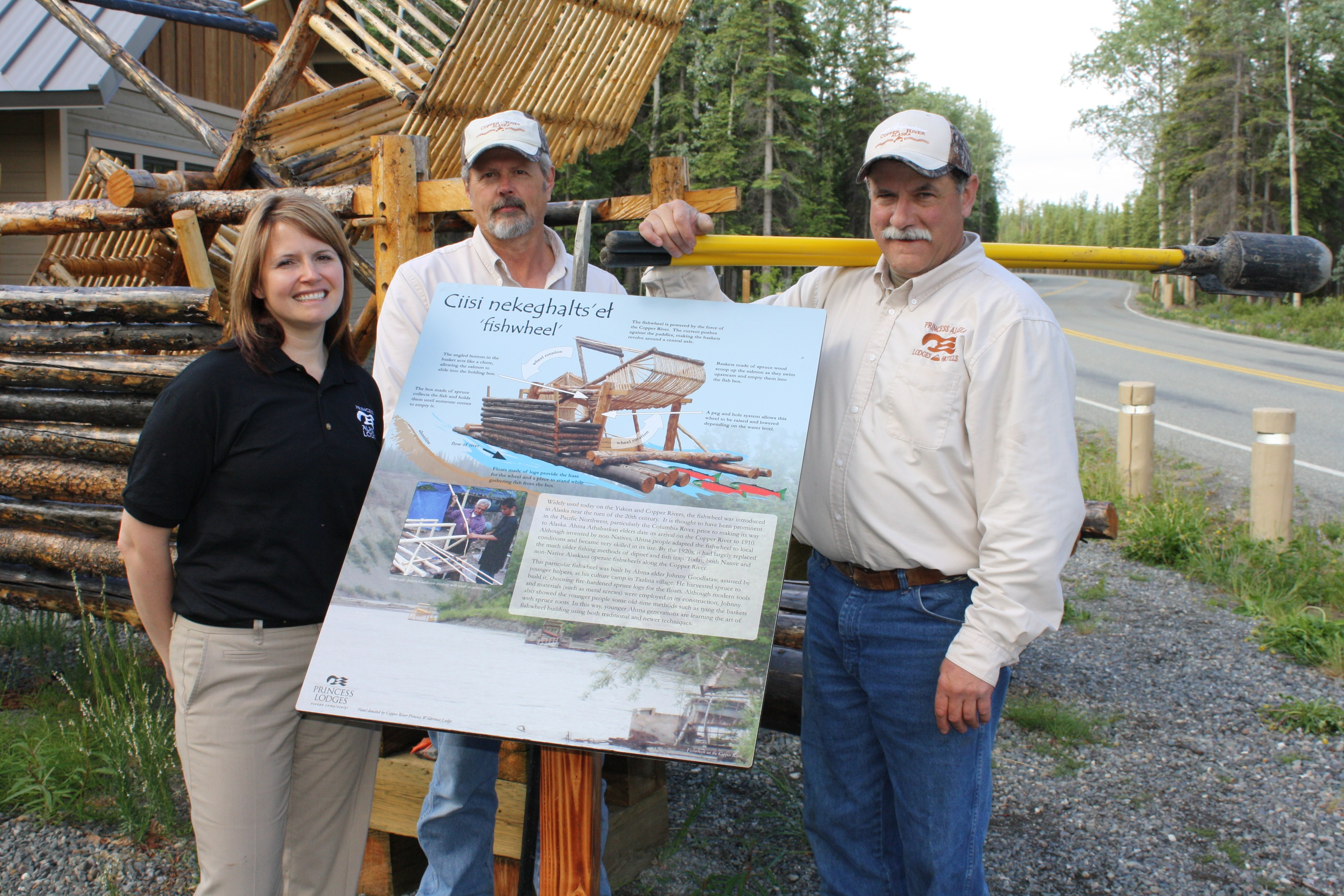 Tracy Smith, Copper River Princess Wilderness Lodge general manager, along with Gregory Sports and Bob Chase of the lodge's maintenance team in front of the new sign and fish wheel.