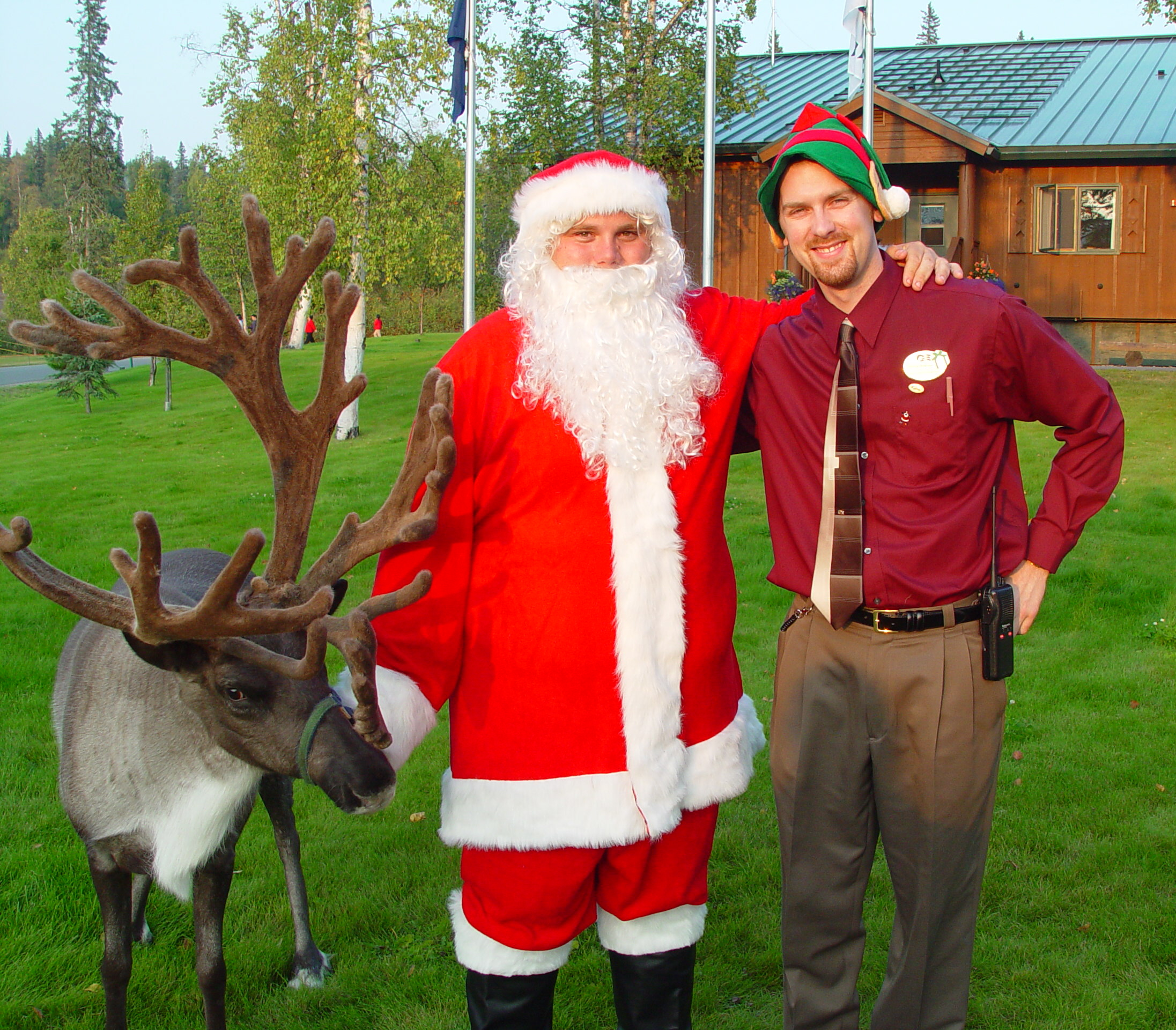 Lodge staff wearing an elf hat posing for a photo with Santa and a reindeer with large, velvety antlers.