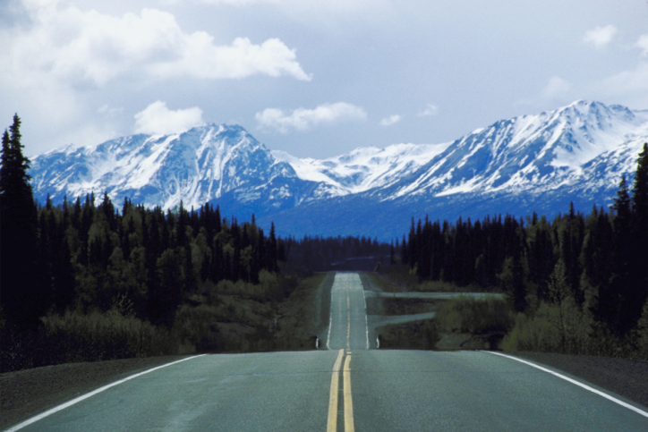 Highway in Alaska that appears to be driving straight toward the mountains.