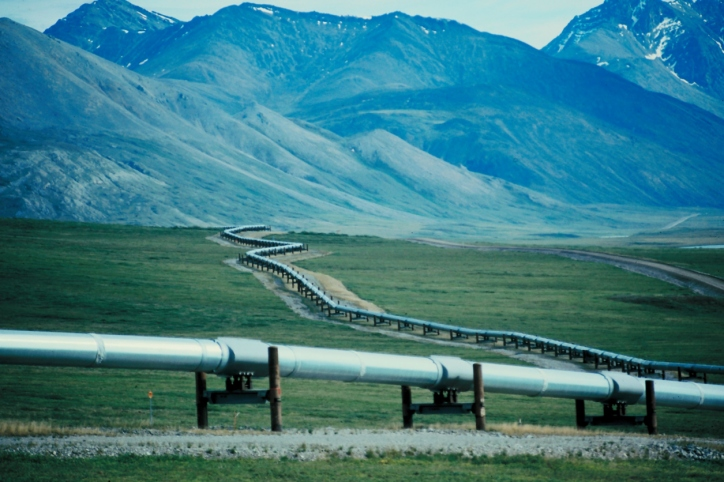 The trans-Alaska pipeline zig-zagging across the terrain with mountains in the background