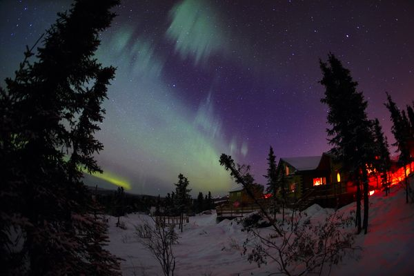 fish-eye photo of the aurora glowing green in a purple sky over a home with lights glowing