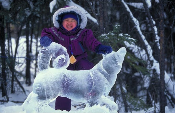 Young girl with a big smile touching a wolf ice sculpture