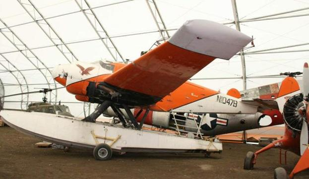 orange and white float plane with wheels parked in a hanger