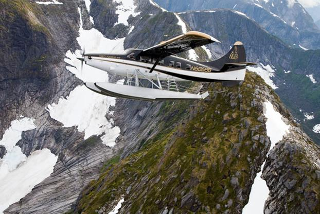close-up photo of a float plane flying with jagged mountains behind