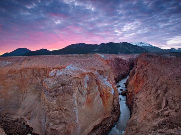a steep, narrow river canyon cuts through reddish orange rock with mountains and a pink sunset behind