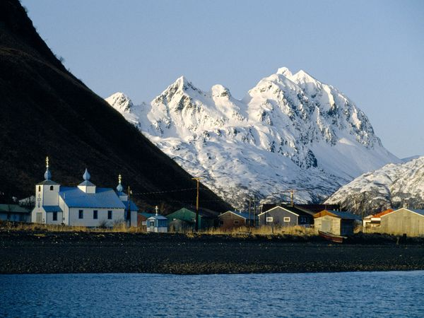 snow covered mountain behind a fishing village and russian church