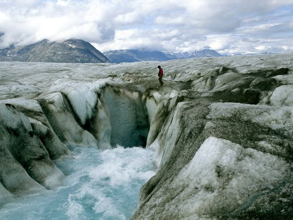 a man hiking across a glacier with rapids running below.