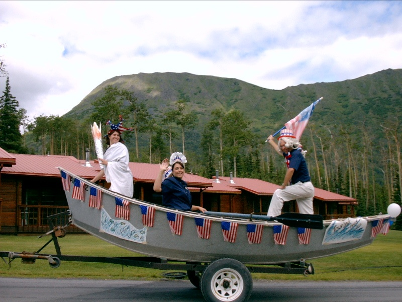 Employees ride in a boat in the parade