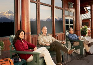 Guests sitting on deck with Denali in window reflection at Mt. McKinley Princess Wilderness Lodge, Alaska