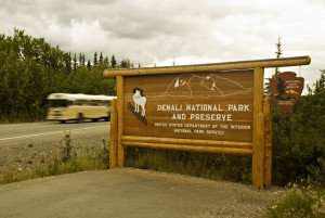 Denali National Park & Preserve Sign at gateway of park with bus in background