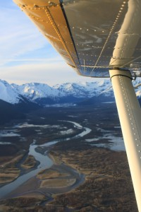 Flight tour above Denali National Park. View of wing over winding rivers and mountain range. Princess Lodges