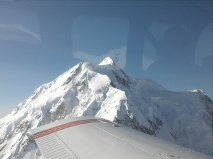 Fixed wing flightseeing tour to face of Mt. McKinley. Seen here, wing of plane and snow covered peak of Mt. McKinley. Princess Lodges