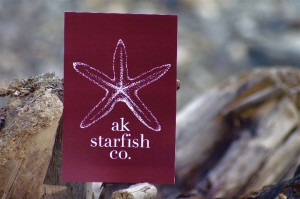 AK Starfish Logo of Starfish in white on red background sitting on a piece of driftwood, Princess Lodges