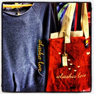 A blue long sleeve shirt and red bag on display with alaska love written on both, Princess Lodges