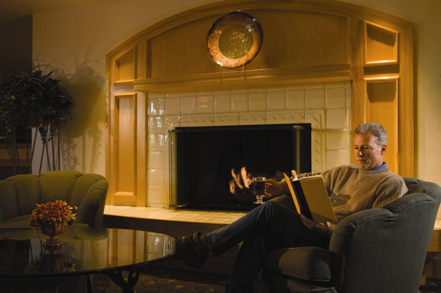 Man sipping coffee and reading book near the fireplace at Fairbanks Princess Riverside Lodge