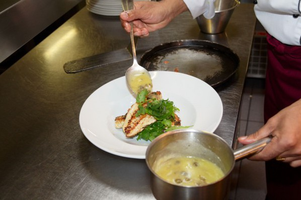 A chef spoons sauce over a dish.