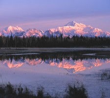 Sun setting on Alaska mountains with reflection on lake.