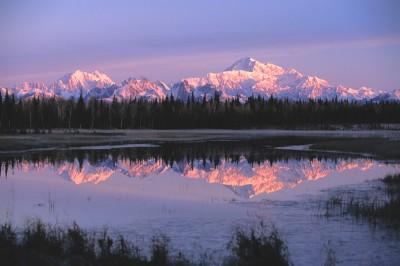 Sun setting on Alaska mountains with reflection on lake.
