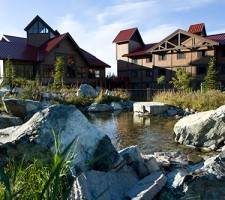Upper building exterior photo at midday at Denali Princess Riverside Lodge
