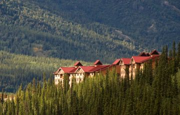 Denali Alaska Wilderness Lodge with sweeping tree-covered hills in the distance