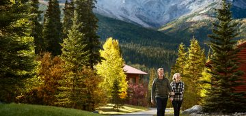 Couple walking the grounds on with fall foliage around at Kenai Princess Wilderness Lodge