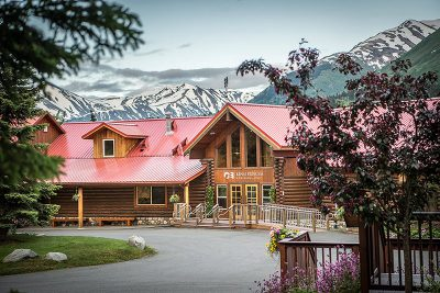 Exterior photo of Kenai Princess Wilderness Lodge shown from the main entrance with mountains behind