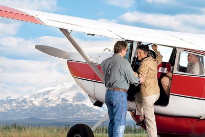 Man helping woman onto plane for a Copper River Lodge excursion