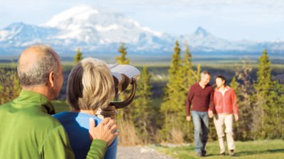 Couple enjoying lookout binoculars at the Copper River Princess Wilderness Lodge