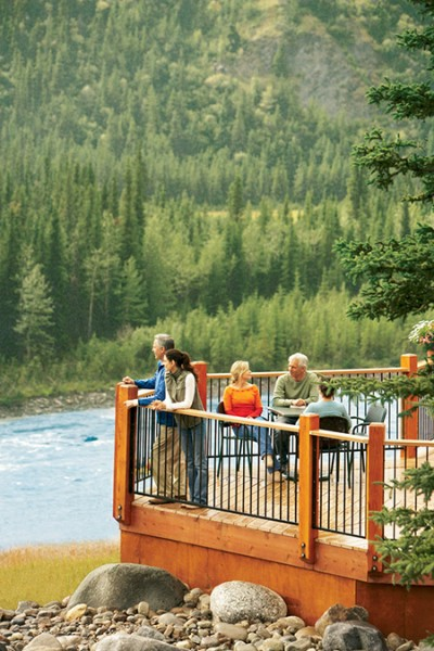 Guests on the deck overlooking the river at the Denali Princess Wilderness Lodge