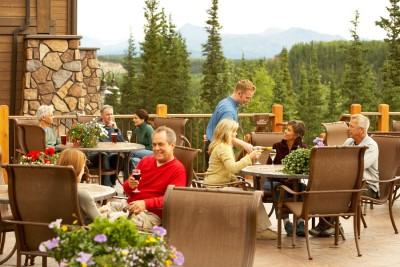Guests at happy hour on the deck of the Denali Princes Wilderness Lodge
