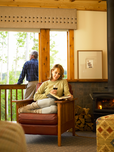 Woman reading and enjoying a glass of wine in a guestroom at the Kenai Princess Lodge