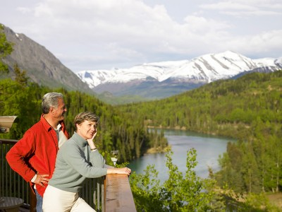 Couple enjoying wine on the Kenai Princess Lodge deck overlooking the river and mountains