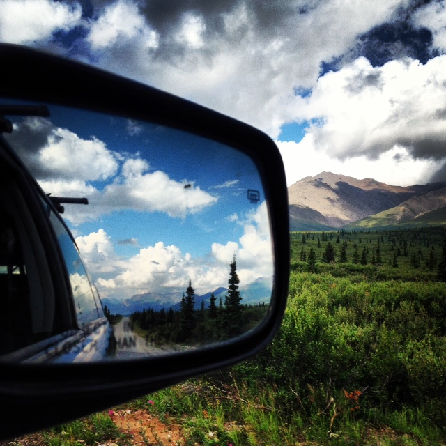 Photo was taken looking into the rearview mirror on a car with scenery of Denali National Park ahead and blue skies behind