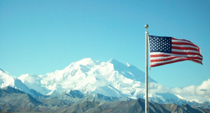 The American flag flies in front of Denali