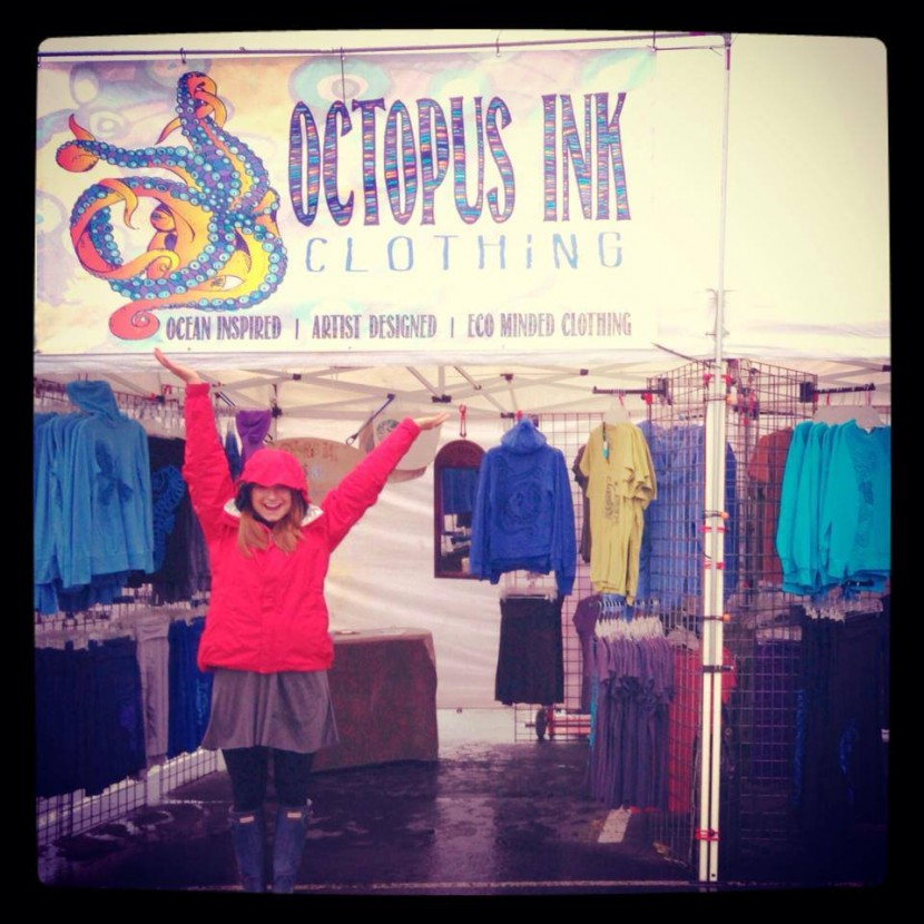 Woman with arms raised in front of booth for Octopus Ink clothing in Anchorage Alaska