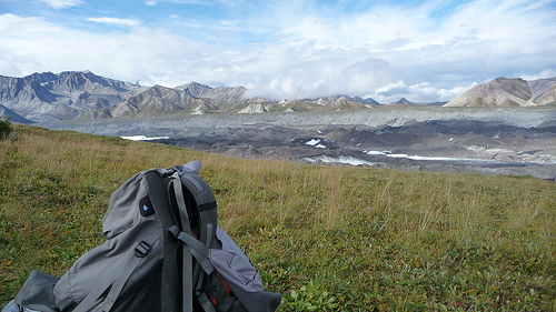 A backpack sits in a foreground of grass while the Alaska range, Mt. McKinley snow capped peaks and Denali rivers are captured in the background - Princess Lodges