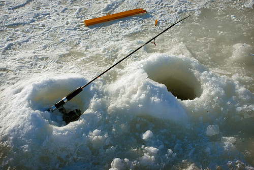 Two holes are cut in ice with a fishing pole standing upright out of the hole on the left.