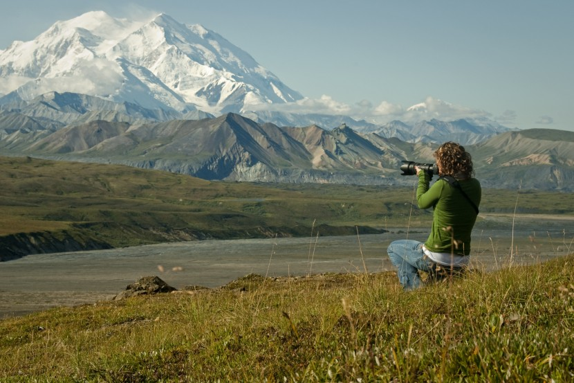 Woman taking photograph of Denali