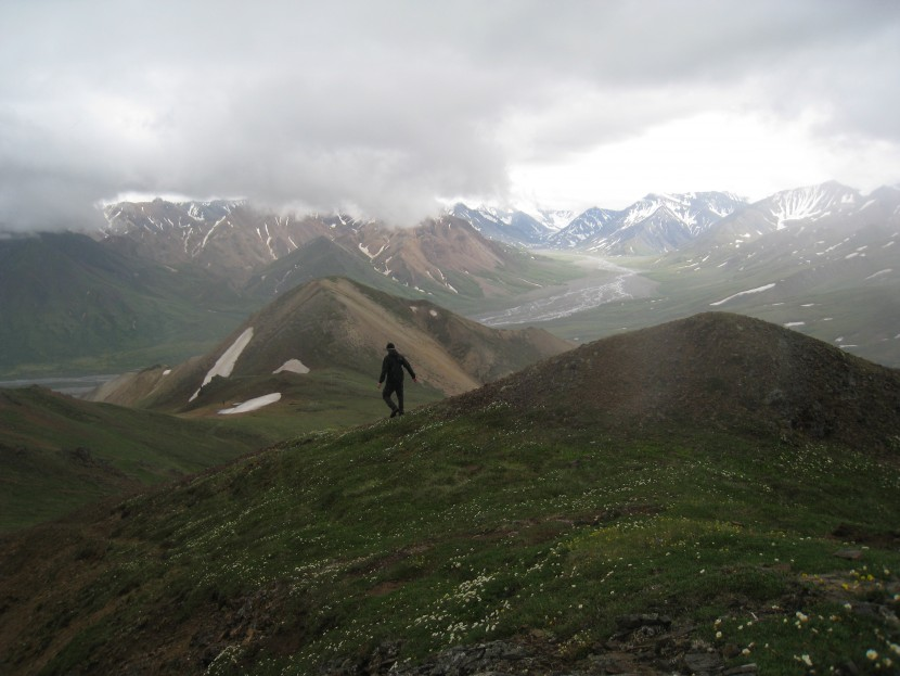 A hiker looks out on a mountain range