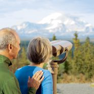 Couple enjoying the views of Mt. Blackburn - woman looking through binoculars on the Copper River Princess property