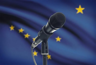 A microphone in front of the Alaska state flag