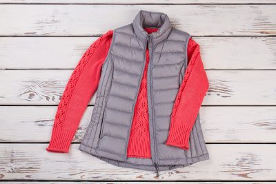 A puffy vest and sweater lay on a background of wood panels