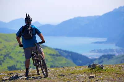 A cyclist pauses to take in the view of a lake at the base of mountains