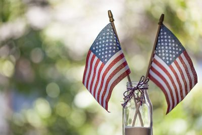 Two small American flags in a decorated mason jar