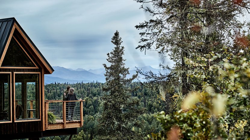Two people stand on the deck of the treehouse at Mt McKinley Princess Wilderness Lodge