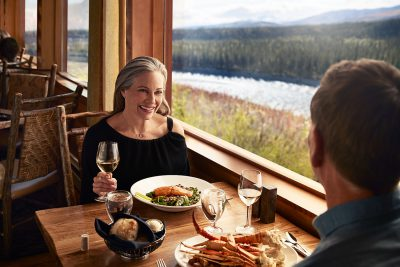 Couple dining at King Salmon Restaurant in Alaska overlooking the Nenana River