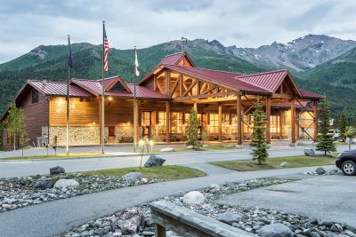 Exterior photo of the Denali Lodge taken at dusk.